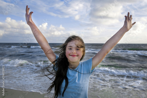 Portrait of down syndrome girl smiling on background of the sea Wallpaper Mural