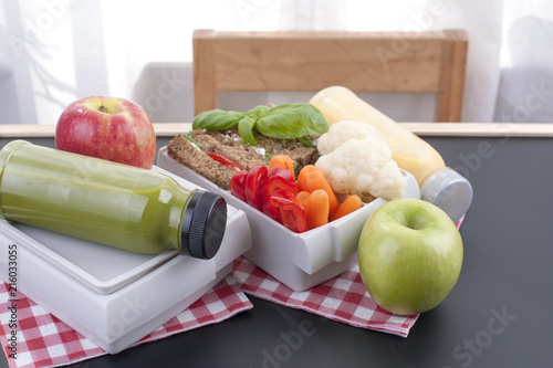 Aluminium Prints Assortment Delicious lunch in a container for school and office. Sandwich, vegetables, apple and green juice for a healthy lunch. Top view on a black background. Food for two