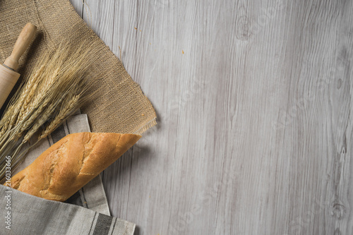 Foto auf AluDibond Brot fresh bread and wheat on sack and wooden table.