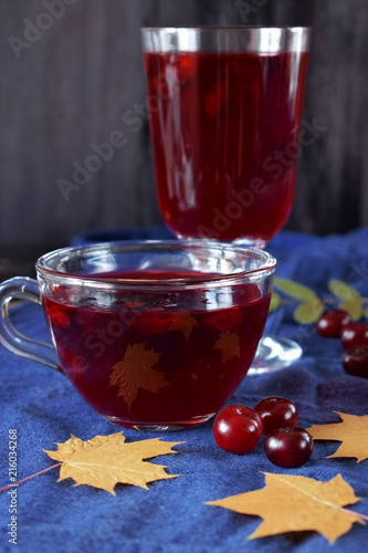 Berry kissel in a glass cup surrounded by autumn leaves and cherries against the blue background