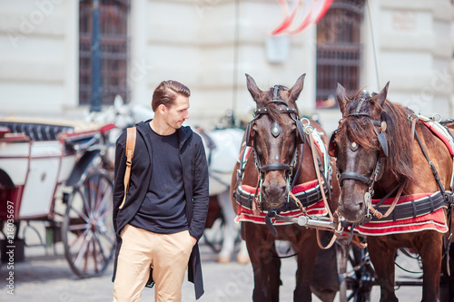 Fotografie, Obraz  Tourist man enjoying a stroll through Vienna and looking at the two horses in th