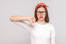 Its Bad, Sad Thumbs Down Of Unsatisfied Emotional Young Woman In White T-shirt With Freckles, Black Glasses, Red Lips And Head Band Looking At Camera. Studio Shot, Isolated On Light Gray Background.