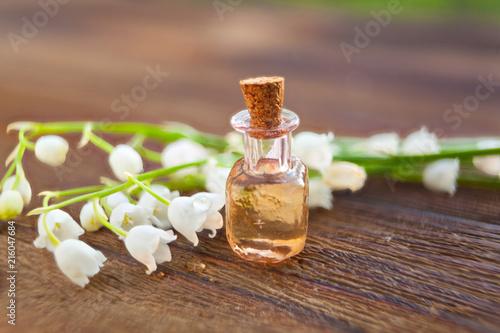Staande foto Lelietje van dalen Essence of flowers on table in beautiful glass jar