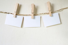 Three Squares Of Blank Paper, Pegged To A String Washing Line, With Wood Plank Fence In The Background.