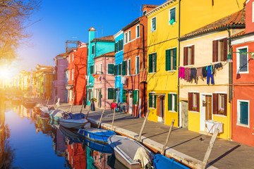 Fototapeta na wymiar Street with colorful buildings in Burano island, Venice, Italy. Architecture and landmarks of Burano, Venice postcard. Scenic canal and colorful architecture in Burano island near Venice, Italy