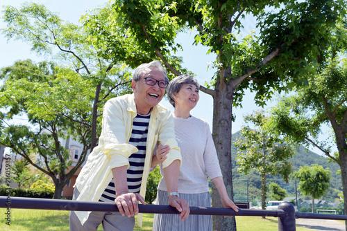 公園で腕を組む笑顔のシニア夫婦