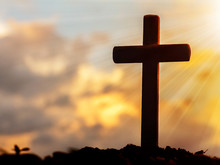 Silhouettes Of Crucifix Symbol With Bright Sunbeam On The Sky