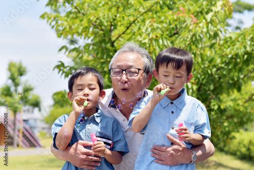 Fotografia  公園でシャボン玉を楽しむ孫を抱きしめるシニア男性