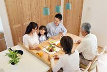自宅で食事を楽しむ3世代家族