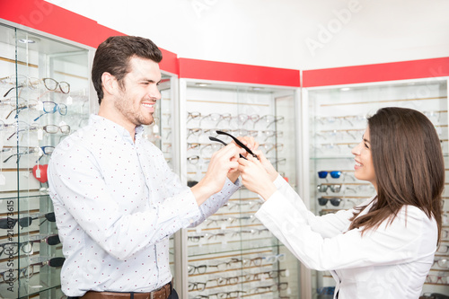 Fotografía  Smiling man being assisted by woman optician in buying new pair of spectacles in