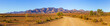 canvas print picture - Gravel countryside road leading to rugged peaks of Flinders Ranges mountains in South Australia