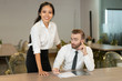 Jolly Asian lady and suspicious male manager in conference room. Cheerful young businesswoman leaning on table and looking at camera. Frowning businessman analyzing papers. Partnership concept