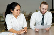 Positive bearded boss and assistant discussing papers and analyzing data. Content bearded man sitting at table and commenting paper while talking to Asian assistant. Paperwork concept