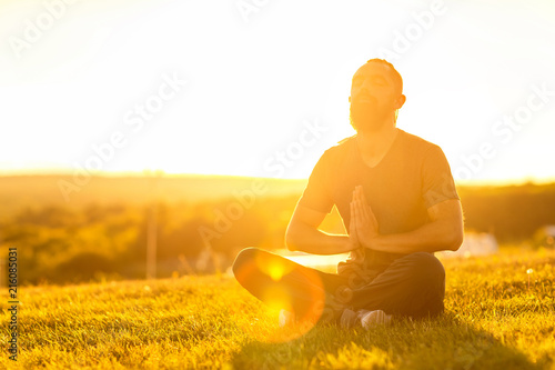 Bearded man is meditating in lotus yoga pose at summer outdoor sunset background sitting at a golden field.