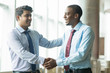 Cheerful young entrepreneur meeting with business partner. Welcoming Indian businessman tapping on shoulder his new coworker. Business relationship concept