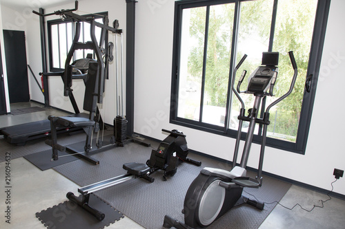 Modern gym room fitness center interior with equipment and