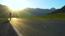 A Lone Young Tourist With A Backpack Walks Along An Empty Asphalt Road In A Mountainous Area. It's Sunset Time.