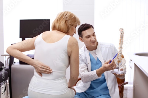 Fotomural Orthopedist showing spine model to patient in hospital