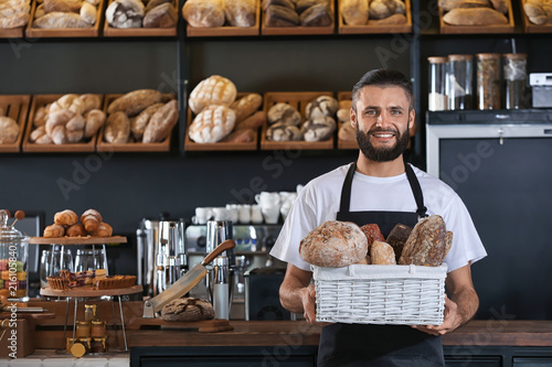 Male baker holding wicker basket with fresh bread in shop Poster Mural XXL