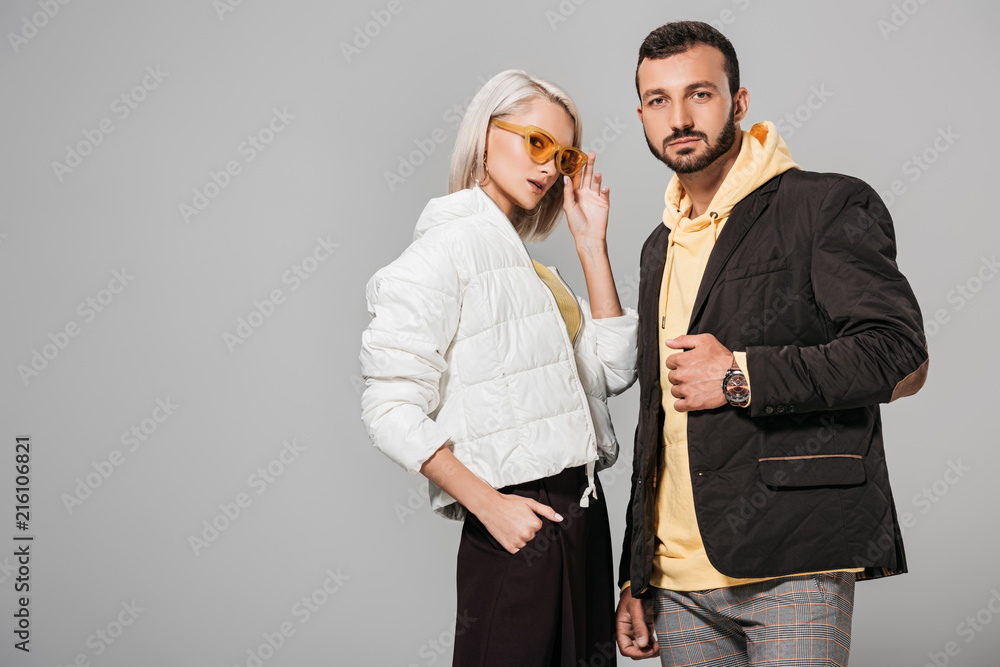 Fototapeta  couple of models in autumn jackets posing isolated on grey background