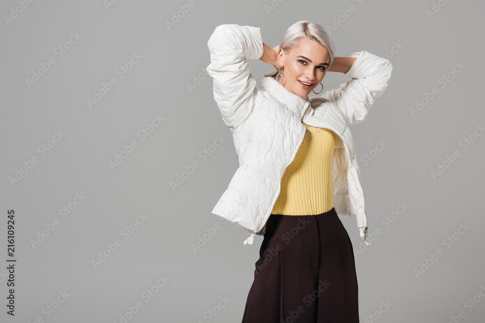 Fototapeta happy female model in stylish autumn jacket posing with raised arms isolated on grey background