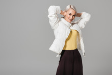 Happy Female Model In Stylish Autumn Jacket Posing With Raised Arms Isolated On Grey Background