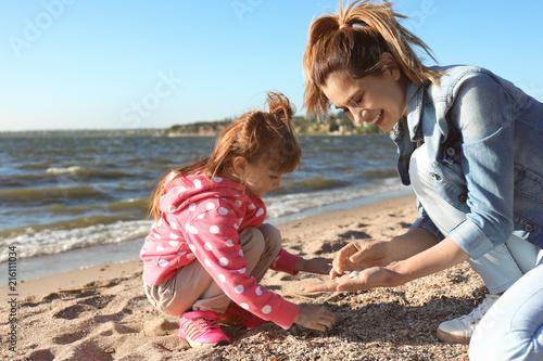 Fotografie, Obraz  Mother and little daughter gathering shells near river