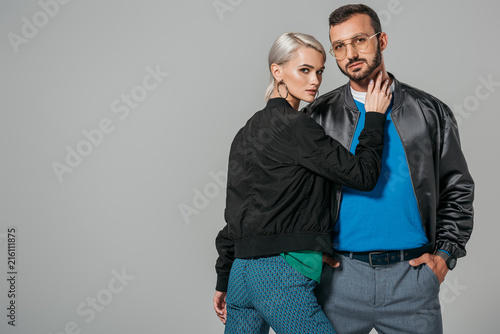 attractive young woman touching neck of stylish boyfriend isolated on grey background