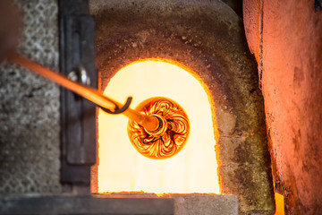 Murano glass-blowing factory. Glass blower forming beautiful piece of glass: put iron rod with attached glass object in furnace to make the glass malleable. Italy
