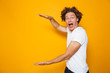 canvas print picture - Young excited man 20s with brown curly hair gesturing aside and holding big copyspace in hands, isolated over yellow background