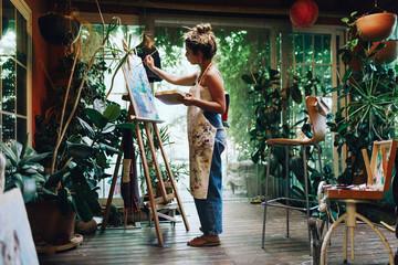 Woman drawing on a camvas in art studio