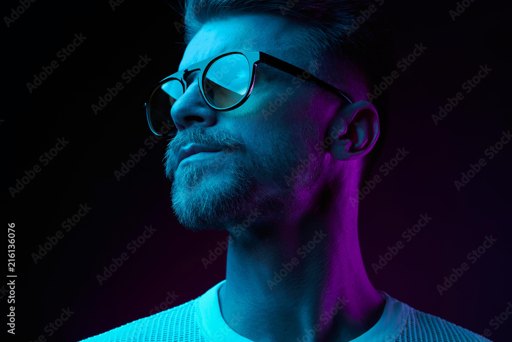 Fototapeta Neon light studio close-up portrait of serious man model with mustaches and beard in sunglasses and white t-shirt