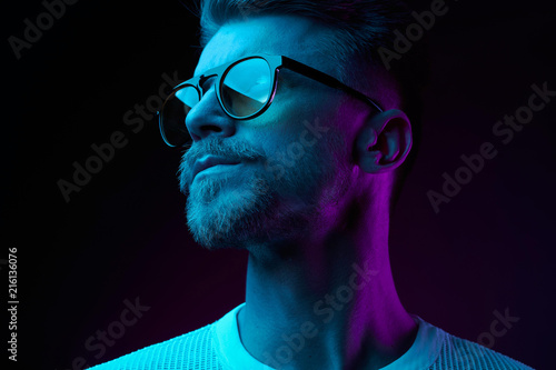 Obraz Neon light studio close-up portrait of serious man model with mustaches and beard in sunglasses and white t-shirt - fototapety do salonu