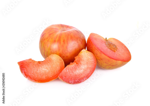 whole and sliced fresh pluot on white background