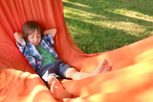 Cute Little Boy Relaxing In Hammock On Sunny Day Outdoors