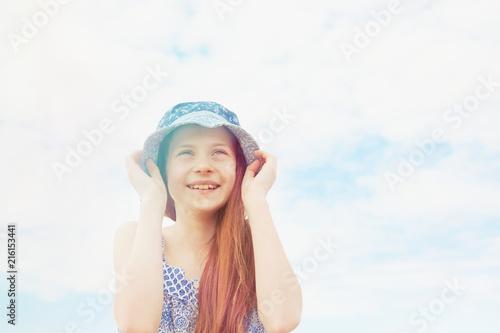 Girl holding down her sun hat