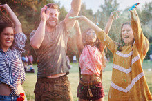 Four Young Adult Friends Dancing And Throwing Coloured Chalk Powder At Holi Festival