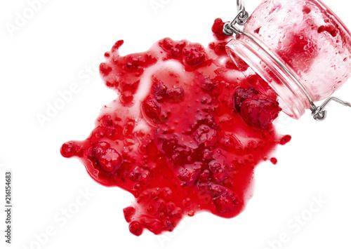 Fotografering  Glass jar and spilled raspberry jam on white background