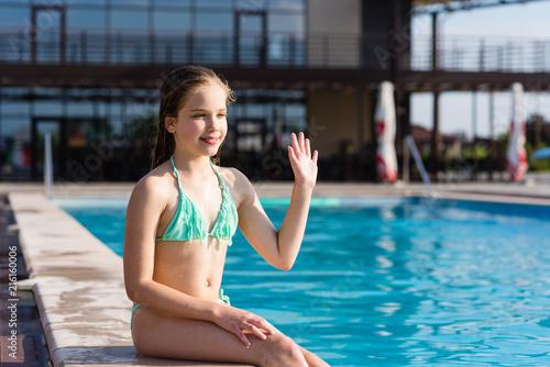 Teenage girl waving hi near pool