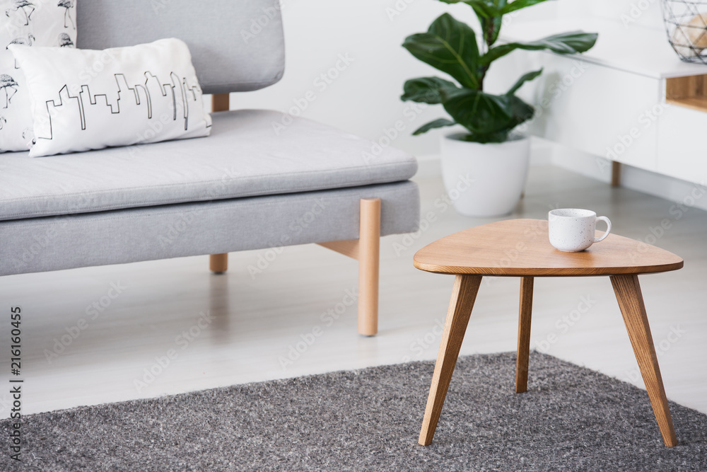 Fototapety, obrazy: Cup on a wooden coffee table and blurry foreground with graphic pillows on a gray sofa in a white living room interior