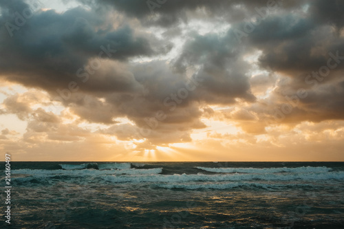 Sun setting over stormy sea