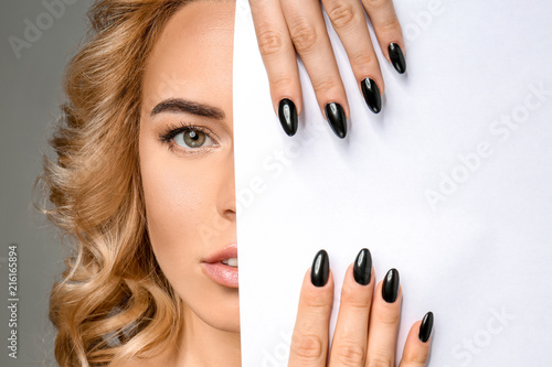 Plakaty do antyram, ramek lub samoprzylepne beautiful-young-woman-with-professional-manicure-and-blank-poster-on-grey-background