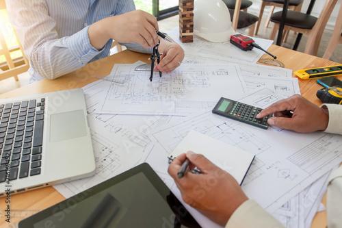 Fototapeta Two architects planning together at desk with blueprints. obraz na płótnie