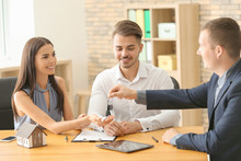 Real Estate Agent Giving Key Of New House To Young Couple In Office