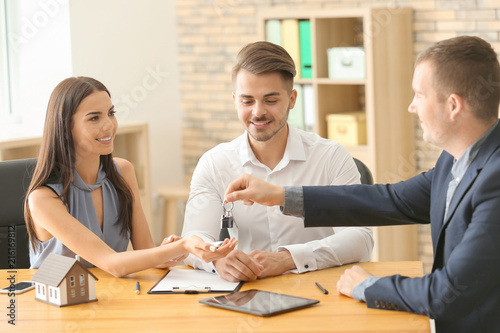 Real estate agent giving key of new house to young couple in office Canvas Print