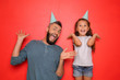 canvas print picture - Funny portrait of father and his little daughter with party hats on color background