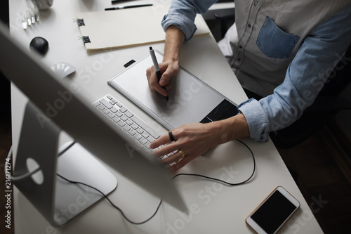 Obraz na plátně Young male designer using graphics tablet while working with com