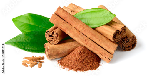 Leinwand Poster cinnamon powder and sticks with fresh leaves isolated on the white background