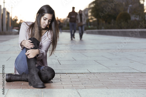 Beautiful girl in boots sitting on the floor.