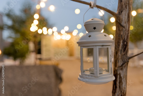 Photo  white candle lantern with summer terrace background. Bokeh